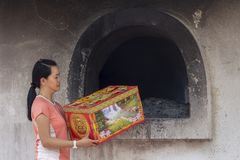 Asian girl offering Spirit money as a gift to the departed during Qing Ming festival. Kuala Lumpur 02 Mac 2018 - Asian woman standing at prayer burner house near Royalty Free Stock Image