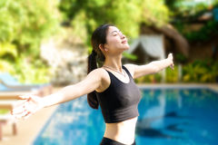 Asian Girl open arms relaxing at pool Royalty Free Stock Image