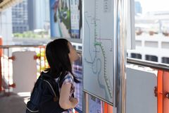 Asian girl orientating herself on the public transport map,Student looks at maps with public transport for travel in the big city. Search transport links on map stock image