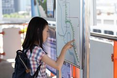 Asian girl orientating herself on the public transport map,Student looks at maps with public transport for travel in the big city. Search transport links on map royalty free stock photos