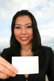 Asian girl outdoors holding card. Asian girl outdoors holding white card Stock Photos