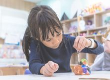 Asian girl painting a doll in Art classroom. Asian girl is painting a doll in Art classroom stock photo