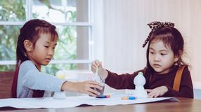 Asian girl painting a doll in Art classroom. Asian girl is painting a doll in Art classroom stock images