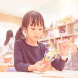 Asian girl painting a doll in Art classroom. Asian girl is painting a doll in Art classroom royalty free stock photos
