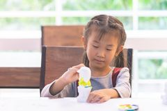 Asian girl painting a doll in Art classroom. Asian girl is painting a doll in Art classroom royalty free stock photography