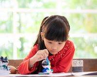 Asian girl painting a doll in Art classroom. Asian girl is painting a doll in Art classroom stock photos