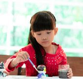 Asian girl painting a doll in Art classroom, for creativity c. Asian girl is painting a doll in Art classroom, for creativity concept royalty free stock photo