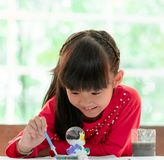 Asian girl painting a doll in Art classroom, for creativity c. Asian girl is painting a doll in Art classroom, for creativity concept stock photography