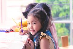 Asian girl painting on paper in Art classroom. Asian girl is painting on paper in Art classroom stock photos