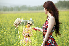 Asian girl painting in rape field Stock Image
