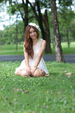 Asian girl in park. A beautiful asian girl is sitting in park Stock Photography
