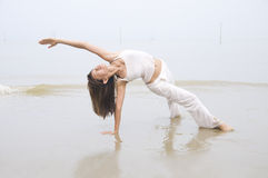 Asian girl performing yoga on a beach Stock Images