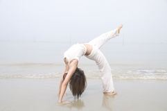 Asian girl performing yoga on a beach Royalty Free Stock Photo