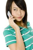 Asian Girl On Phone. An attractive young asian woman holding a mobile phone and looking away from camera royalty free stock photos