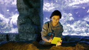 Asian girl photographs on the tablet of small fishes stock footage