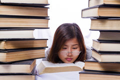 Asian girl in pile of books. On white background Royalty Free Stock Photo