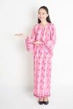 Asian girl in pink batik dress showing somethings Stock Photos