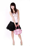 Asian girl with pink handbag. A beautiful Asian girl with pink handbag on white background Royalty Free Stock Photography