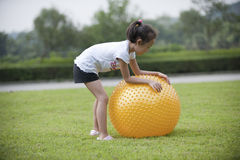 Asian girl play ball in the grass Royalty Free Stock Photo