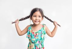 Asian girl play funny action with her pony hair. On white background Royalty Free Stock Photos