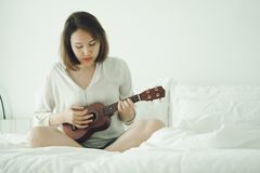 Asian girl Play the guitar from the morning wake up. Making it feel bright and soothing music can develop the brain and mind.