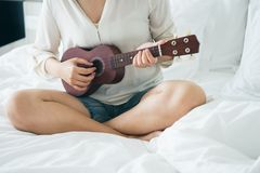 Asian girl Play the guitar from the morning wake up. Making it f