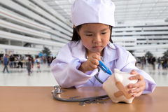 Asian girl playing as a doctor care Piggy Bank.  Stock Photography