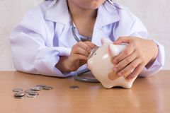 Asian girl playing as a doctor care Piggy Bank. Asian girl playing as a doctor care Piggy Bank Stock Image