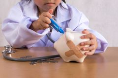 Asian girl playing as a doctor care Piggy Bank. Coin Stock Photo