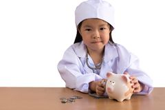 Asian girl playing as a doctor care piggy bank, isolated. Background with clipping path Royalty Free Stock Photo
