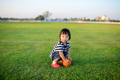 Asian Girl Playing Ball In Green Field. Stock Images