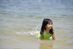 Asian girl playing on the beach in the summertime Stock Images