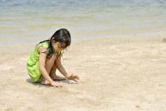 Asian girl playing on the beach in the summertime Stock Photos