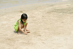 Asian girl playing on the beach in the summertime Royalty Free Stock Images