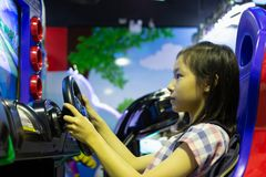 Asian girl playing the car racing game machine at one of the sho stock photography