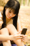 Asian girl playing cell phone Stock Photo