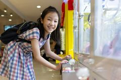 Asian girl playing Claw Game or cabinet catches the doll at one royalty free stock photography
