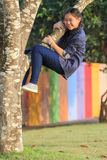 Asian girl playing funny face by climbing on tree branch in publ Royalty Free Stock Photos