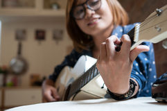 Asian girl is playing the guitar. Close up and selective focus, Asian girl is playing the guitar Stock Photos