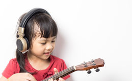 Asian girl is playing Music guitar with headphone on white background Royalty Free Stock Photos