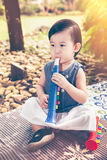 Asian girl playing plastic trumpet pipe. Child spend her free ti Stock Photography