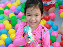 Asian girl playing in a pool with colorful balls Royalty Free Stock Photography