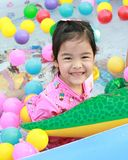 Asian girl playing in a pool with colorful balls Stock Photos