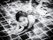 Asian girl is playing in the pool, laying down Stock Images