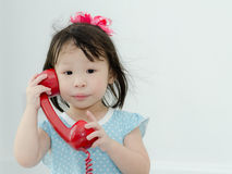 Asian girl playing red retro phone at home Royalty Free Stock Photo
