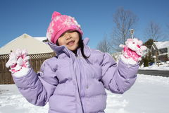 Asian girl playing in snow with gloves up stock images