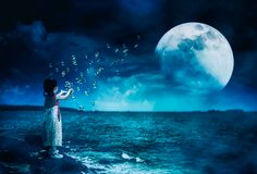 Asian girl playing with soap bubbles. Super moon behind partial royalty free stock photography