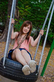 Asian girl playing a swing. A cute Thai girl playing a swing Stock Photography