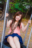 Asian girl playing a swing Royalty Free Stock Photography