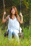 Asian girl playing swing in a park Royalty Free Stock Photos